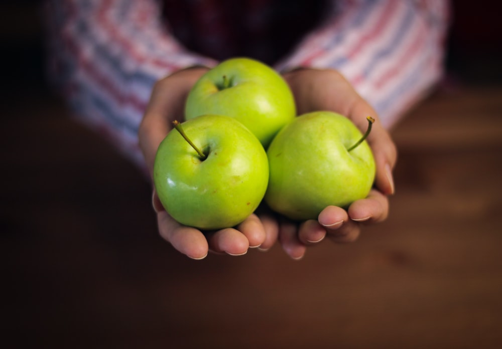 green apples on brown wooden table