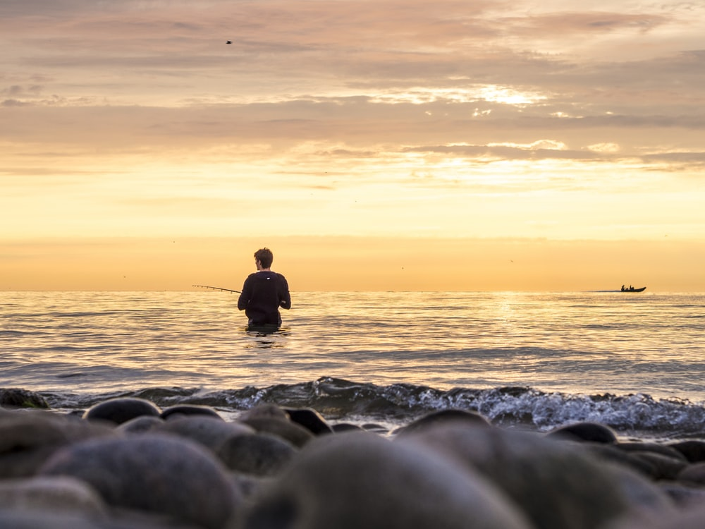 silhouette of man sitting on rocky shore during sunset