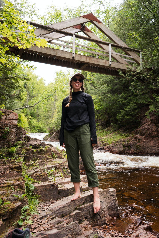 woman in black jacket standing on brown wooden bridge