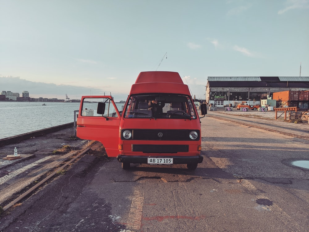 red van on road near body of water during daytime
