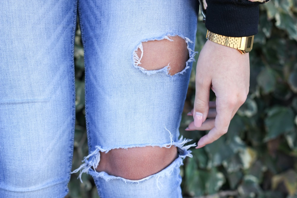 person in blue denim jeans with brown band on left hand