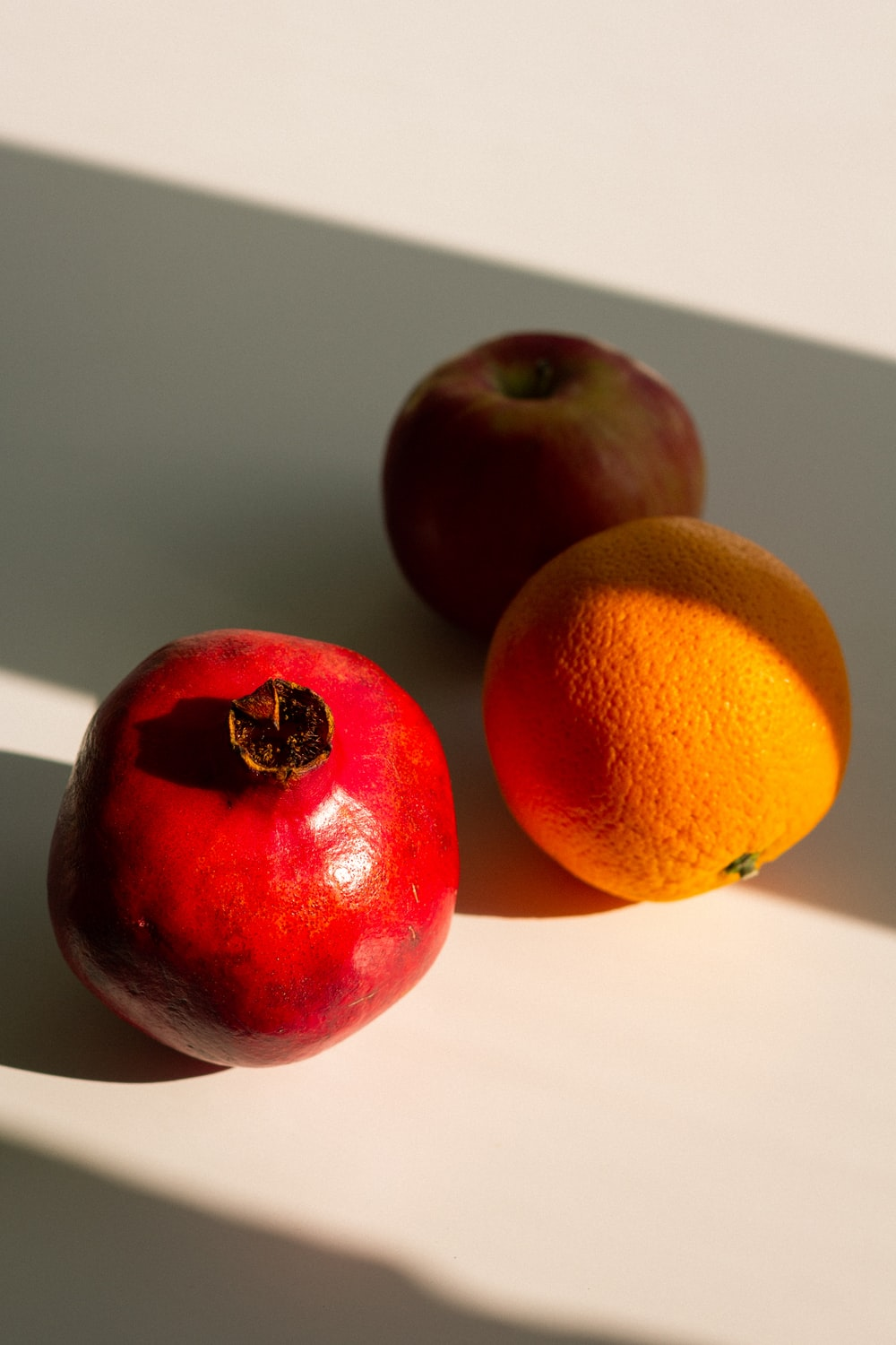 orange and apple fruits on white table