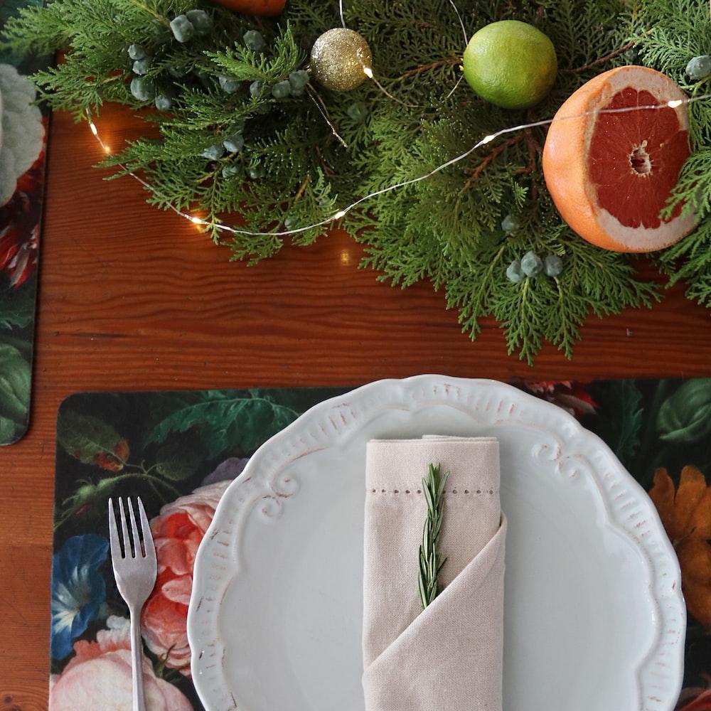 sliced apple on white ceramic plate beside silver fork and knife