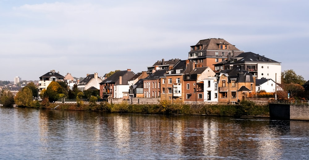 brown and white concrete houses beside river during daytime
