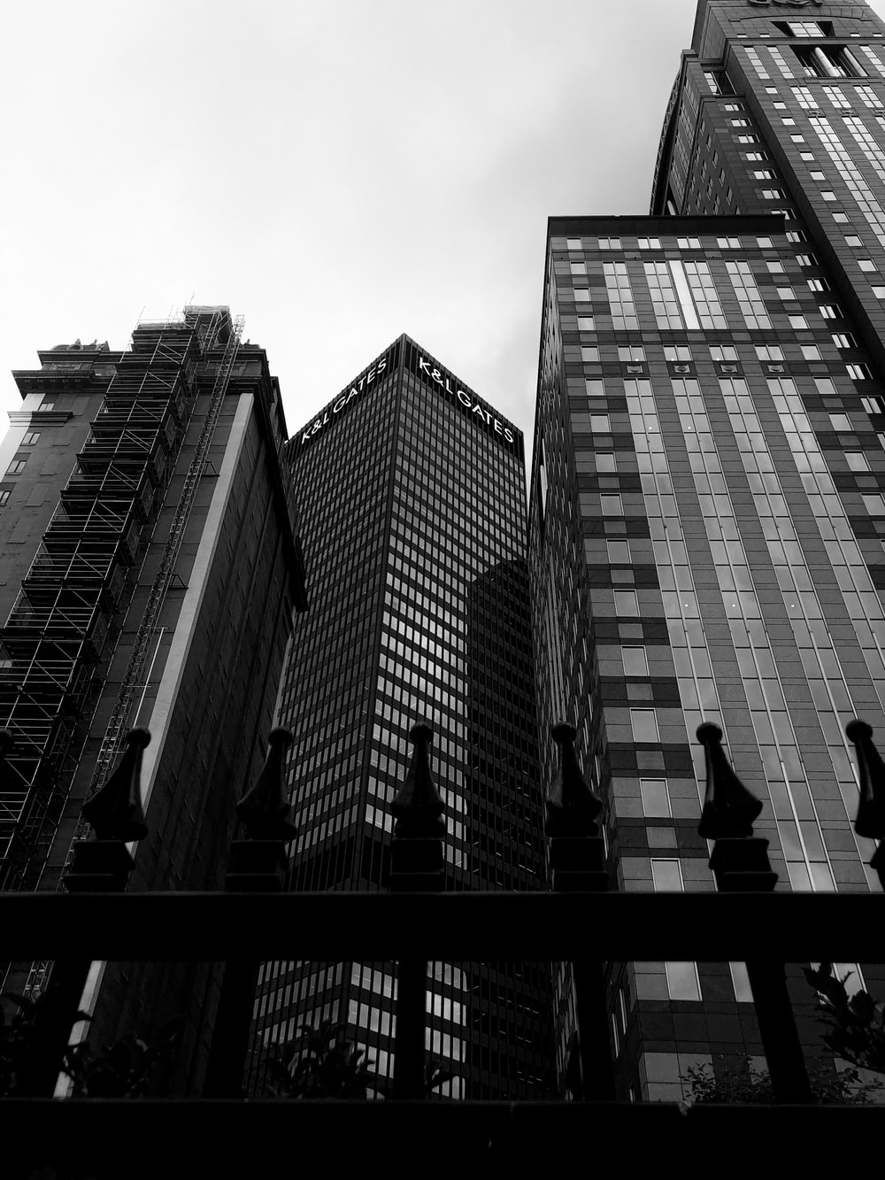 grayscale photo of man and woman kissing on top of building