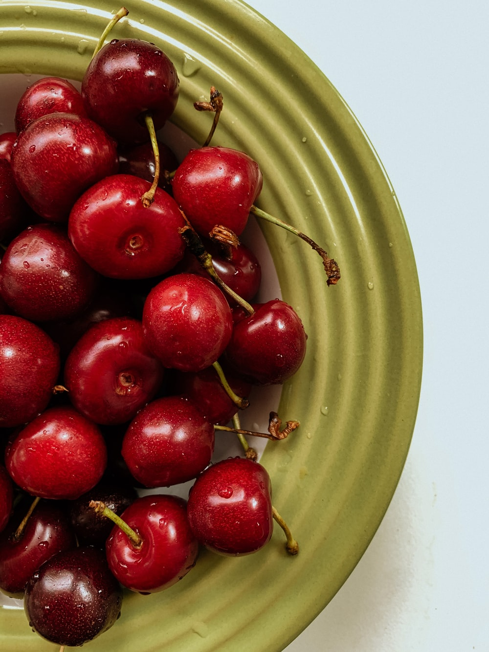 red round fruits on green round plate