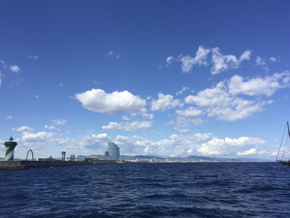 white ship on sea under blue sky and white clouds during daytime