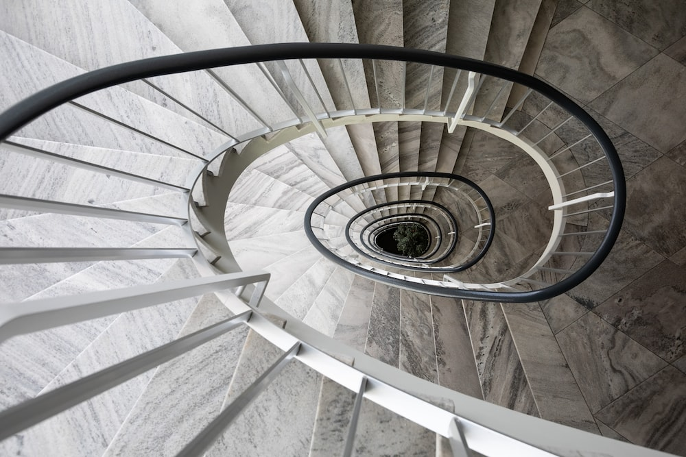 white spiral staircase with gray metal railings