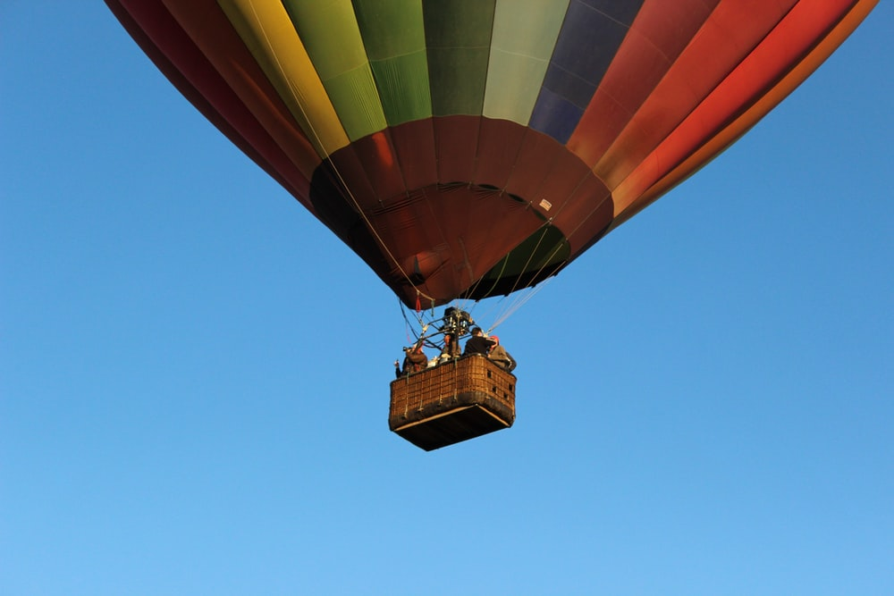 orange and yellow hot air balloon in mid air during daytime