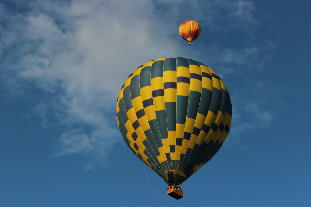 green and yellow hot air balloon in mid air