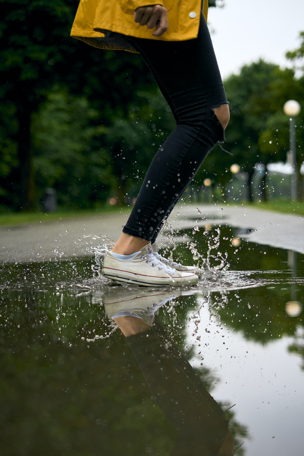 person in black leggings and white sneakers jumping on water