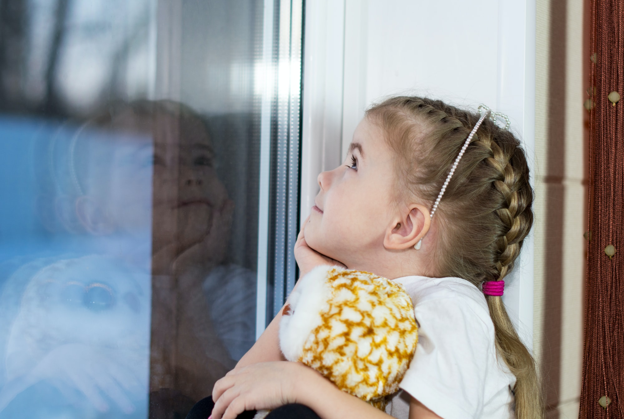 A little girl with a toy sits on the windowsill and draws on the window