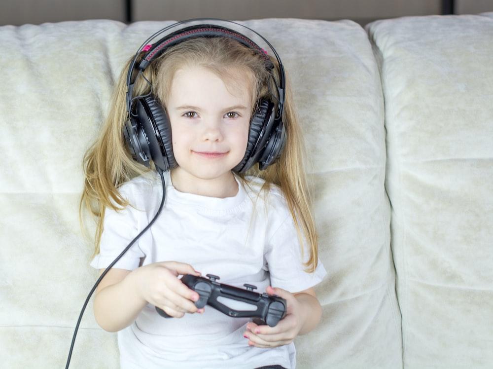 girl in white crew neck t-shirt lying on bed using black headphones