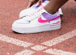 person wearing white and pink nike sneakers