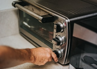 person holding stainless steel gas stove