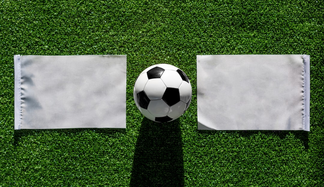 Top view ball with mockup flag match on Green grass football