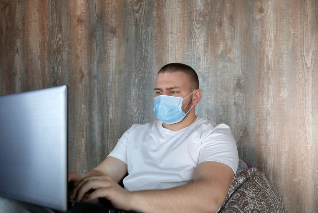 Man in medical mask with a laptop in the house. Coronovirus and home office