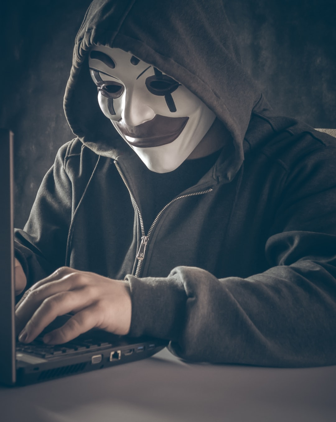 Anonymous computer hacker in white mask and hoodie.