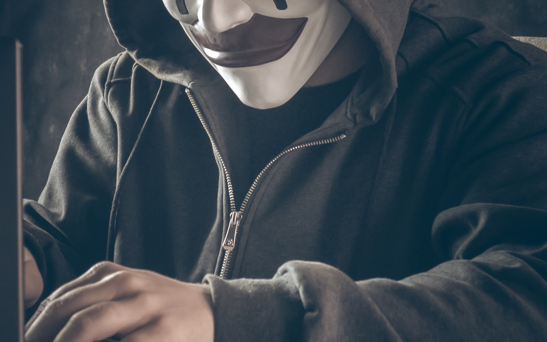 person in black hoodie wearing white mask