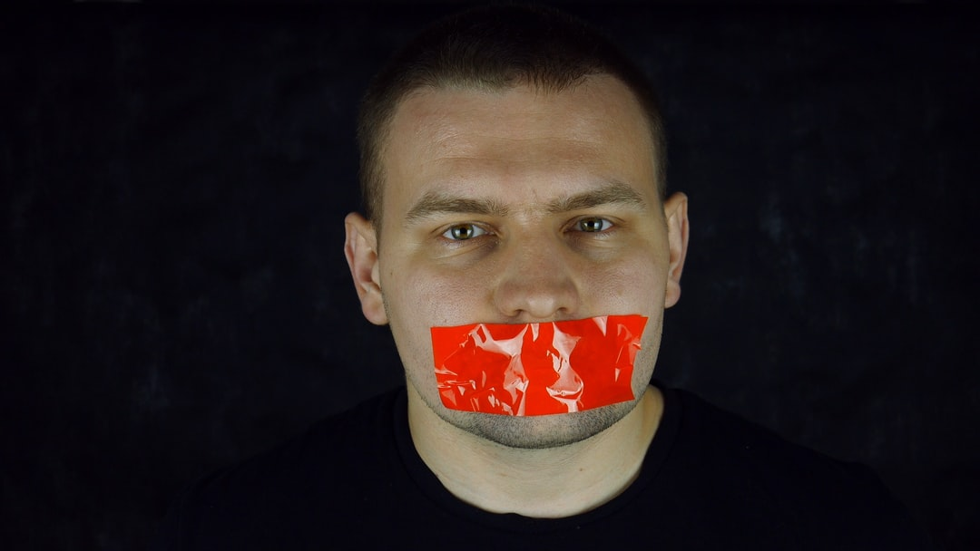 Man with orange scotch-tape on his mouth on black background. Censorship concept