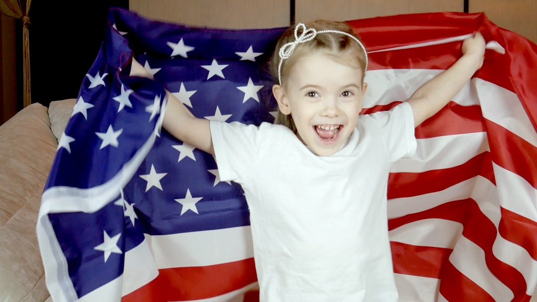Happy pretty, little girl jumping with USA flag, cheering for favorite football team