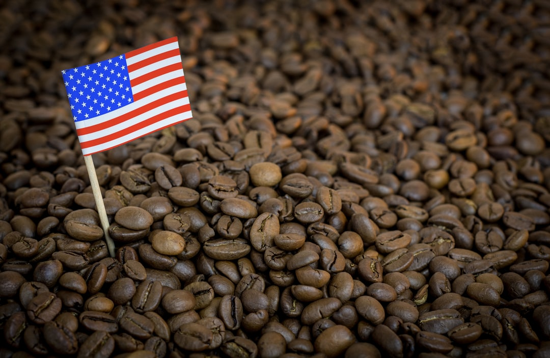 USA flag sticking in roasted coffee beans. The concept of export and import of coffee