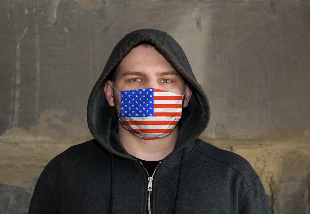 Man Wearing a hood and a USA flag Mask to Protect him