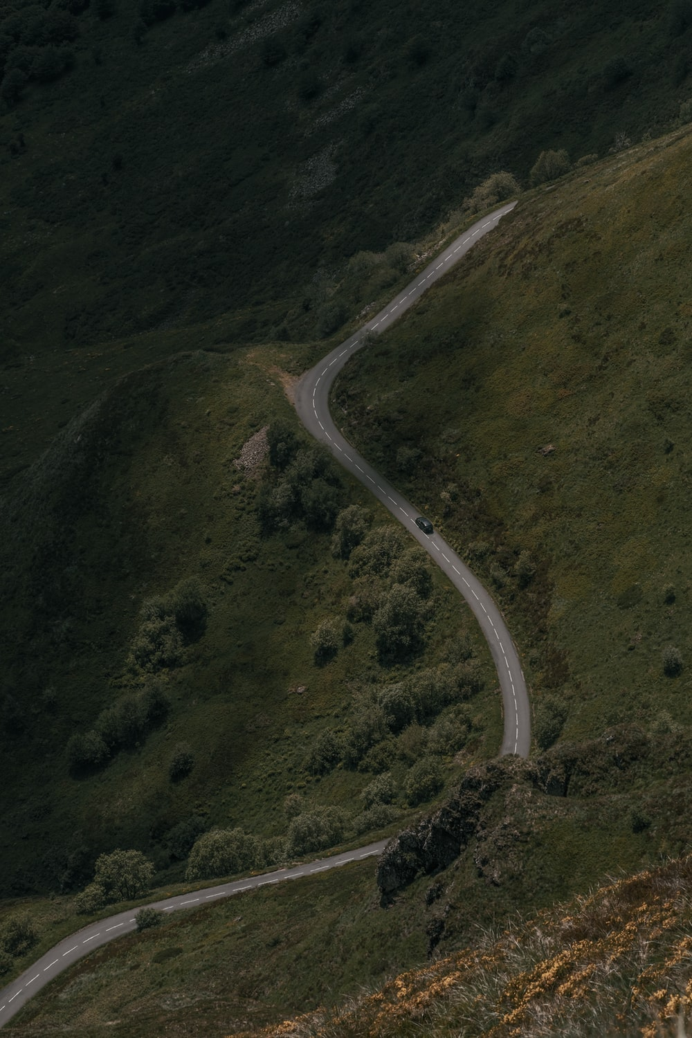 aerial view of road in the middle of green mountains
