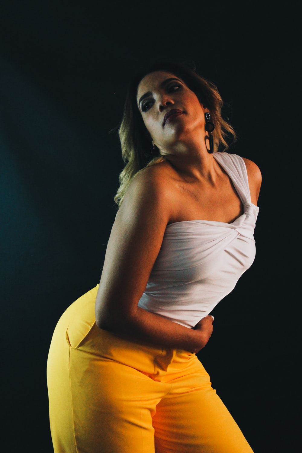 woman in white tank top and yellow pants