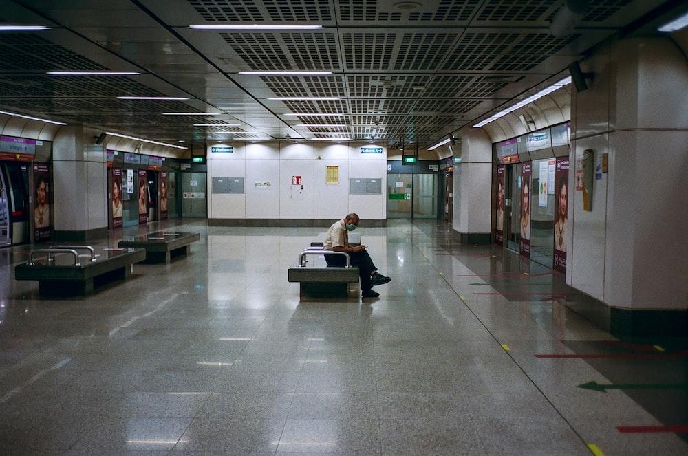 man in white shirt sitting on black bench