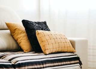 brown throw pillow on white and blue bed linen