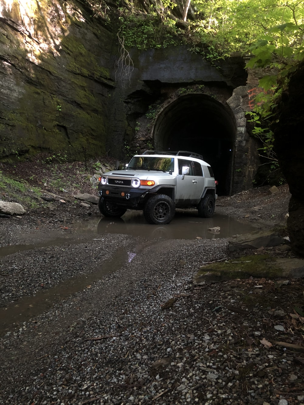 white suv parked near gray rock formation during daytime