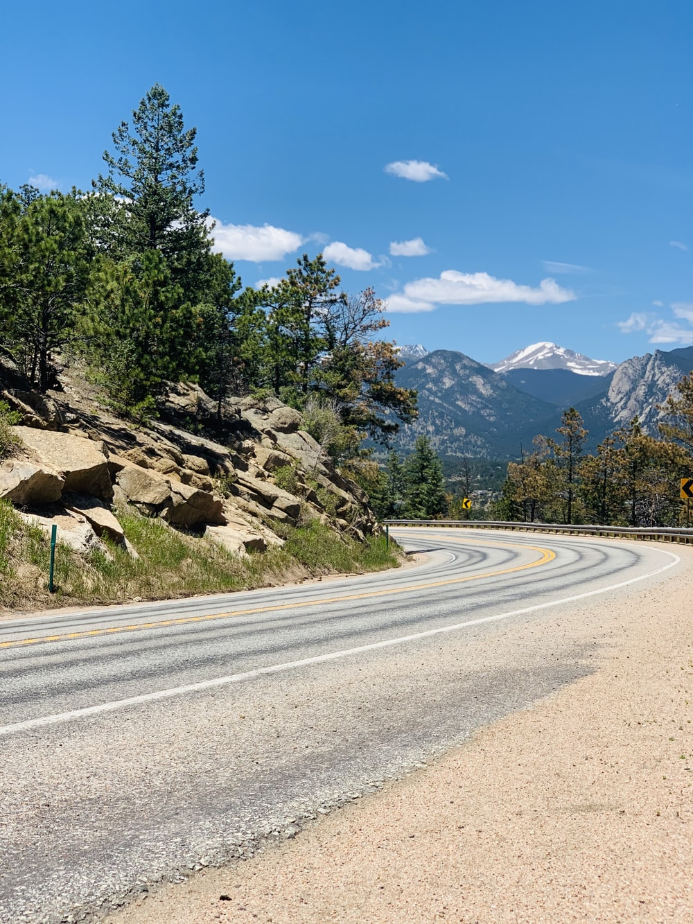 gray asphalt road near green trees and mountain under blue sky during daytime