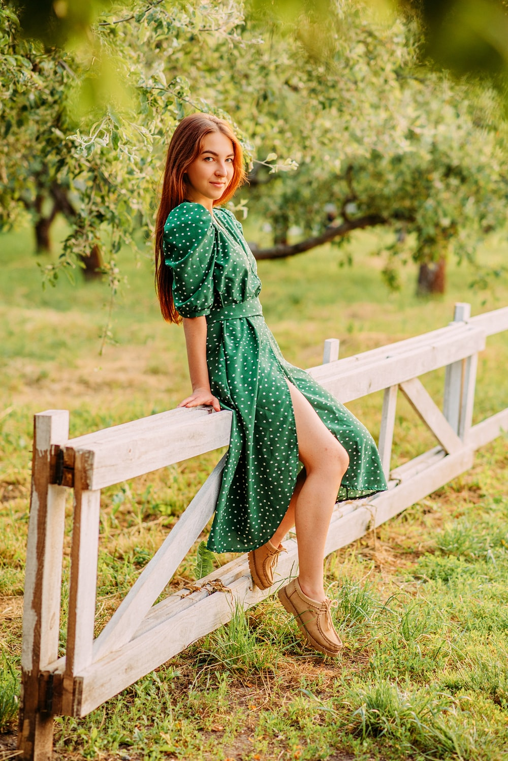 woman in green dress standing on brown wooden bridge during daytime