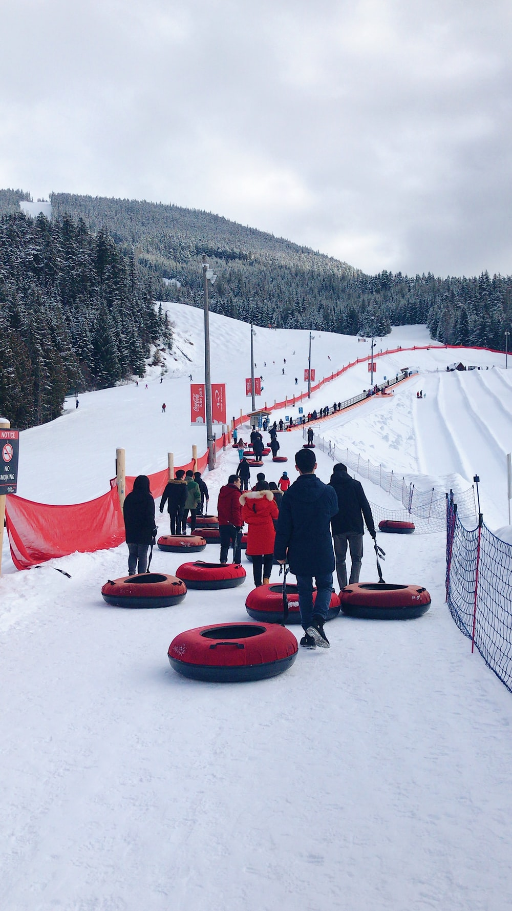 people sitting on red sled on snow covered ground during daytime