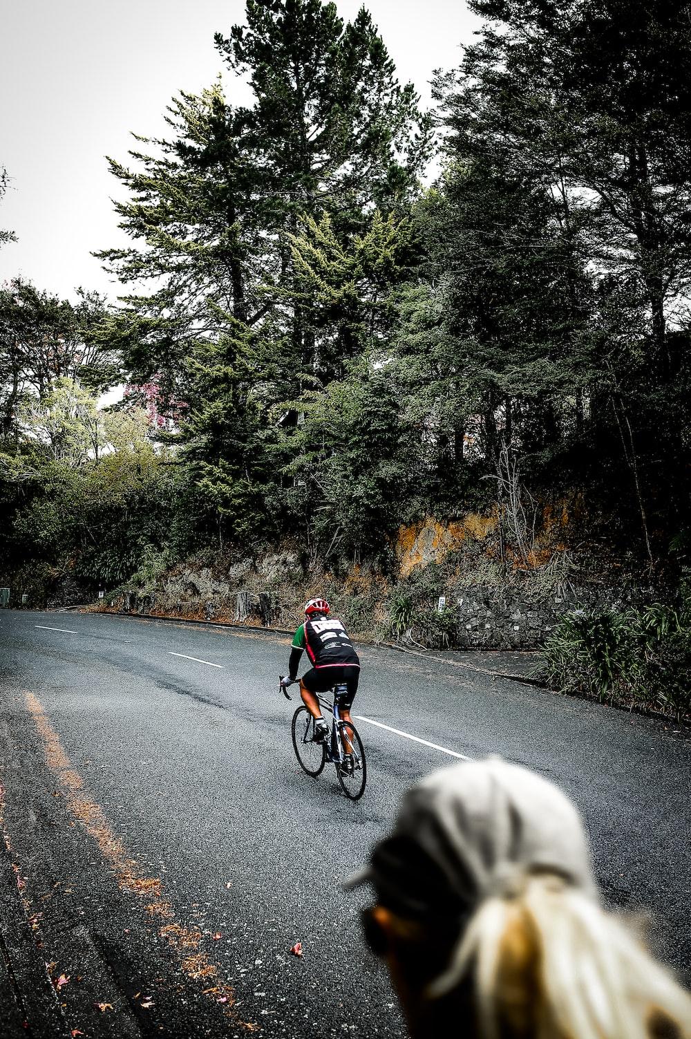 man in black shirt riding bicycle on road during daytime