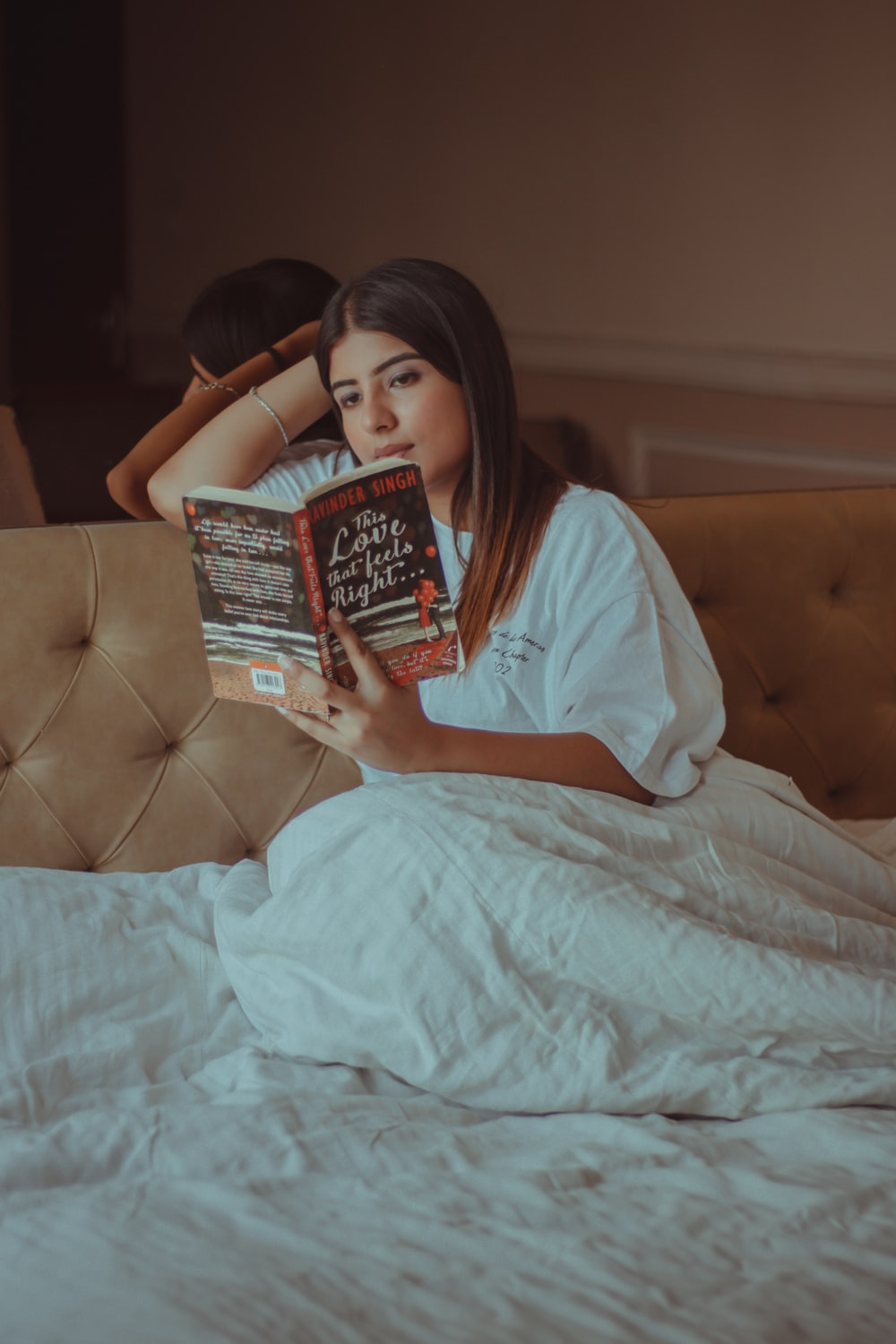 woman in white shirt holding book