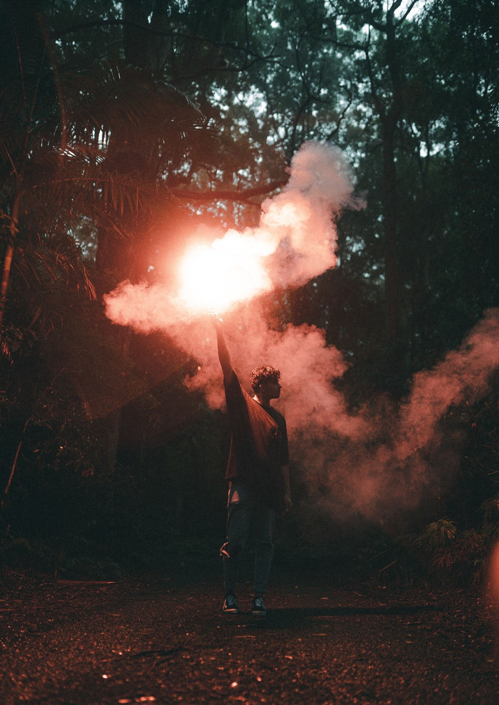 man in black jacket standing near fire