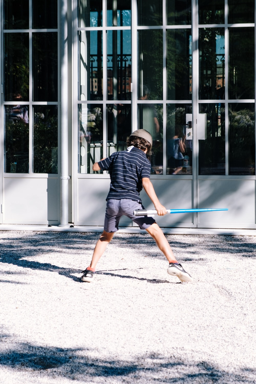 man in black and white stripe shirt and black shorts walking on sidewalk during daytime