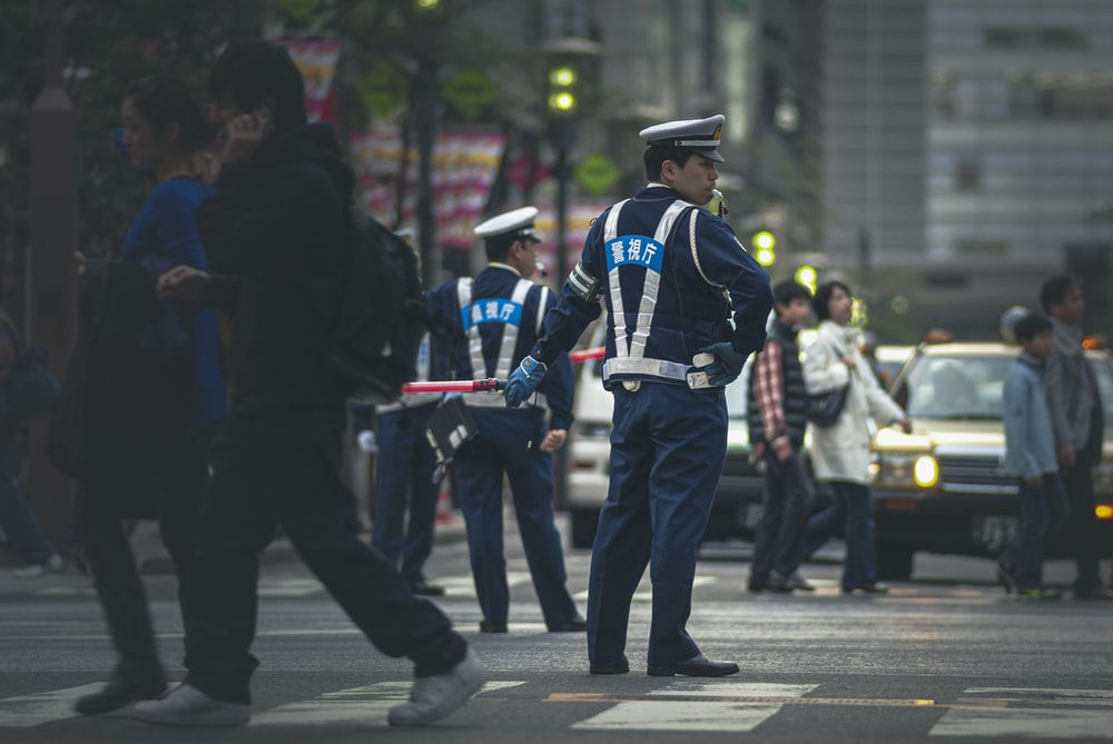man in blue and white police uniform standing on gray asphalt road during daytime