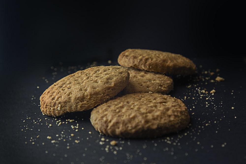three brown cookies on black surface