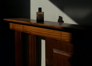 brown wooden table with black bottle on top