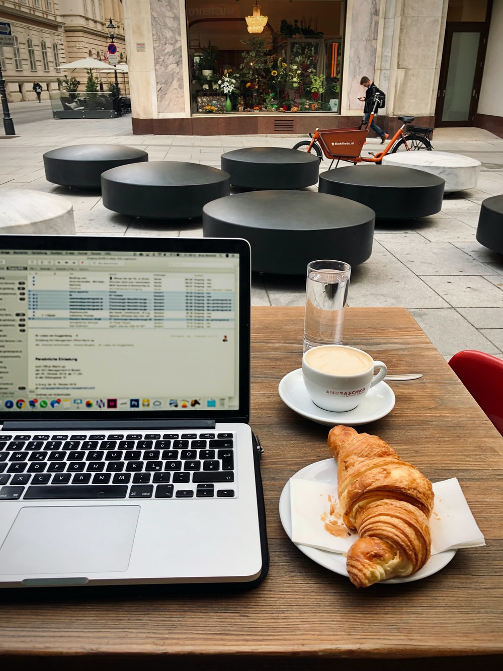 macbook pro beside white ceramic bowl with bread