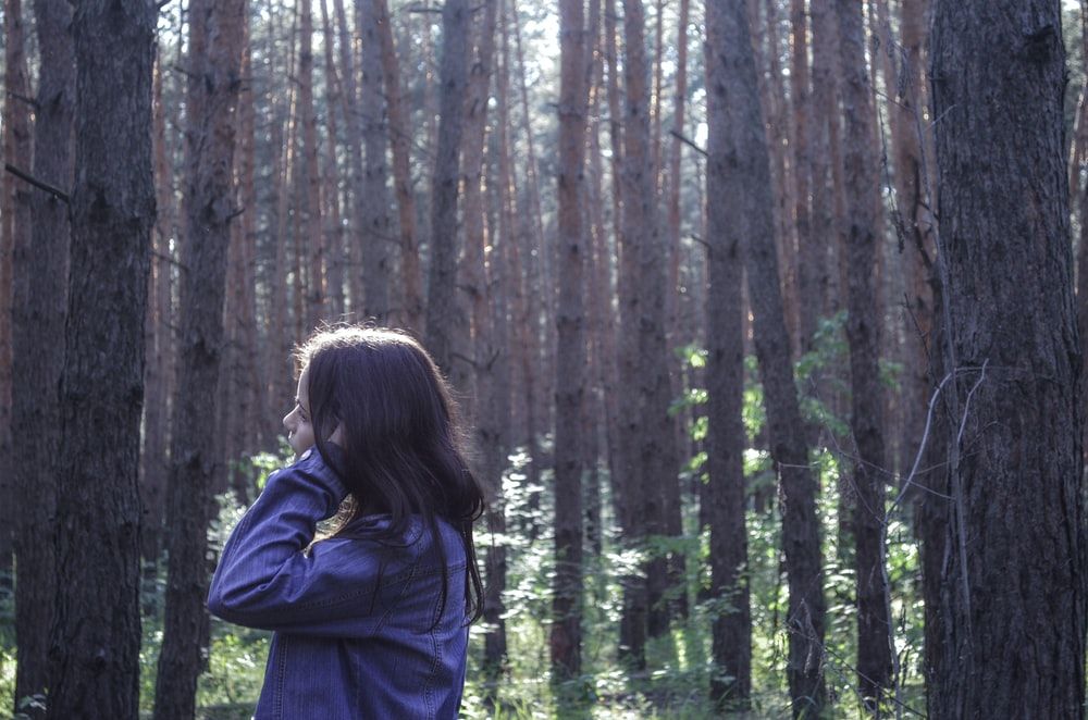 woman in blue jacket standing in the woods