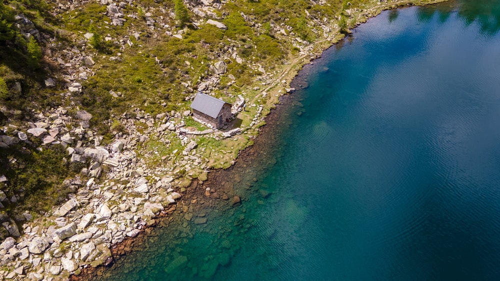 aerial view of house on hill beside body of water during daytime