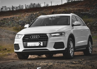 white audi a 4 on dirt road during daytime
