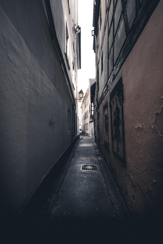 empty hallway between brown brick wall