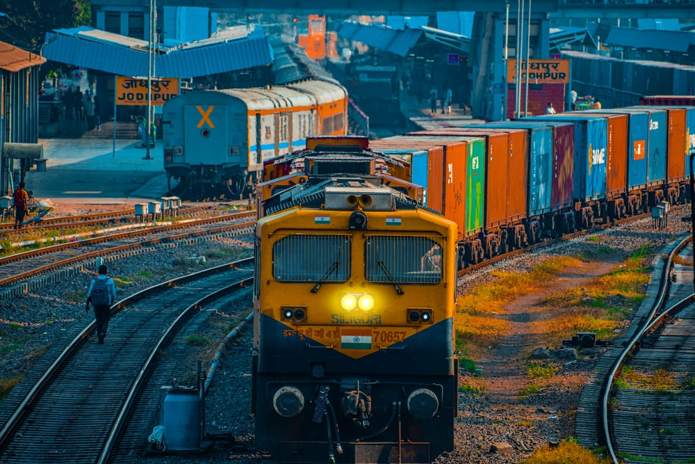 yellow and black train on rail tracks during daytime