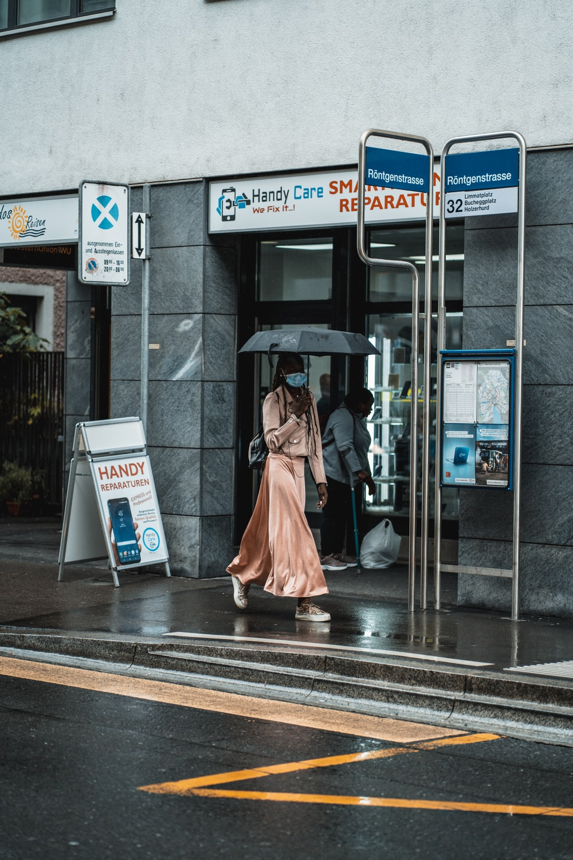 woman in pink dress walking on sidewalk during daytime