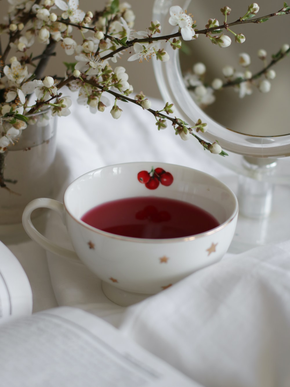 white ceramic teacup with red liquid inside
